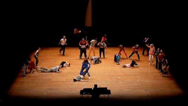 Tänzer und Tänzerinnen bewegen sich oder liegen auf einer Holzbühne
