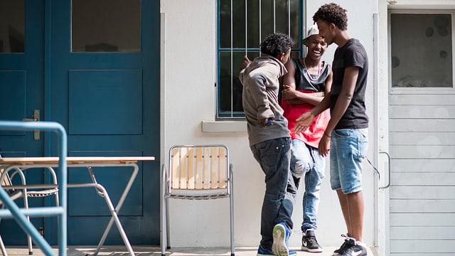 Drei jugendliche Flüchtlinge stehen vor einem weissen Gebäude mit blauer Tür