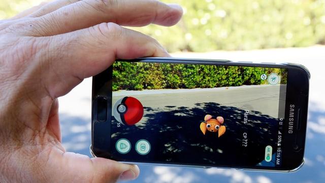 In maun che tegna in telefonin, sin lez è avert il gieu Pokémon Go.