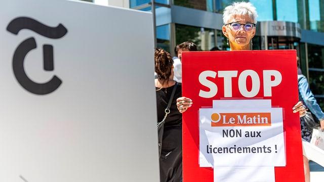 Frau neben Tamedia-Logo stehend. Sie hält ein Plakat in den Händen.