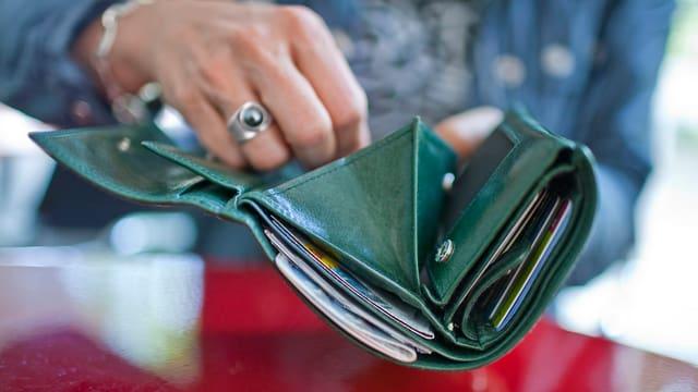 Ein Portemonnaie in den Händern einer Frau.