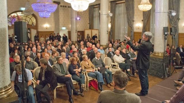 Dieter Kohler steht auf dem Podium und bietet den Gegnern von Rheinhattan an mitzudiskutieren.