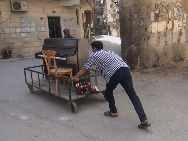 Ein Musiker schiebt ein Klavier durch die zerstörten Strassen Syriens.