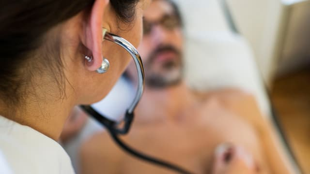 Symbolbild: Eine Ärztin hört den Brustkorb eines Patienten ab, dieser liegt auf dem Untersuchungstisch.