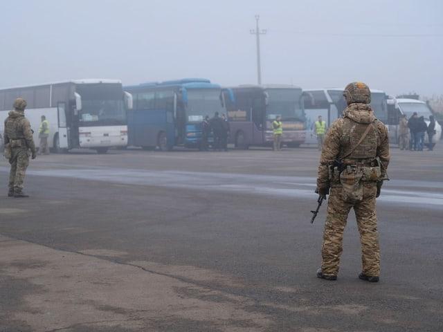 Ukrainische Soldaten postieren sich vor den Bussen, die die Rebellen nach Hause bringen sollen.