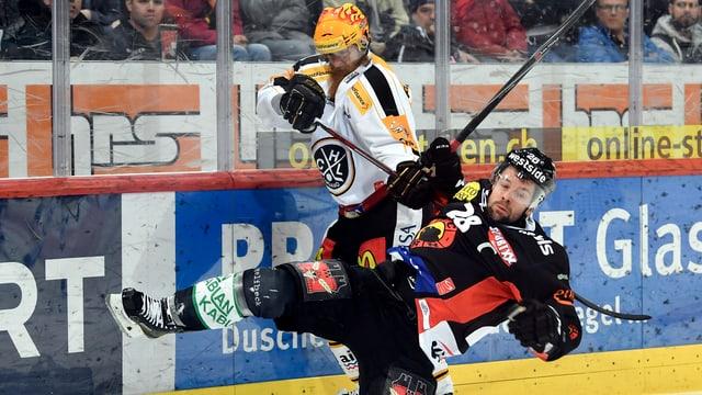 2 giugaders da hockey en in duell.