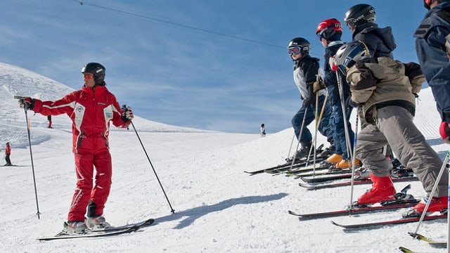 Ein Skilehrer steht vor einer Guppe Kinder im Schnee.
