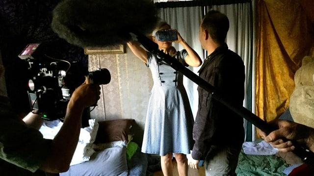 Eine Frau trägt eine VR-Brille. Eine Crew filmt sie.