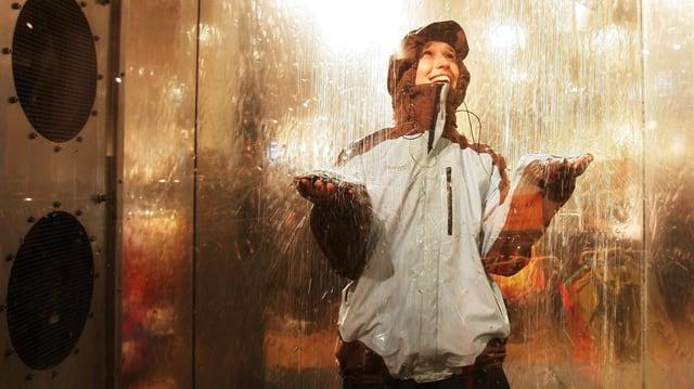 Eine Frau in einer Regenkabine.