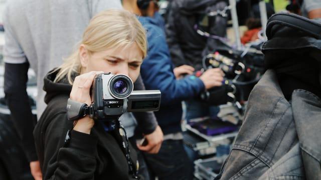 Eine junge Frau hält eine kleine Videokamera in der Hand