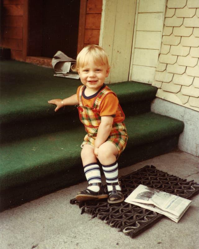 Ein kleiner Bub mit orangem T-Shirt und kurzer karierter Hose sitzt auf der Stufe einer grünen Treppe.
