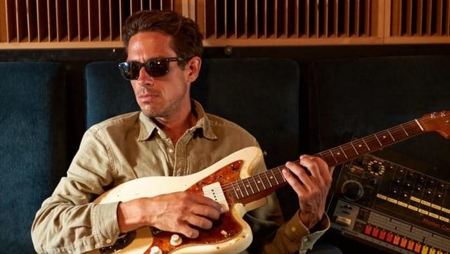 Ein Mann mit Sonnenbrille zupft an seiner Gitarre.