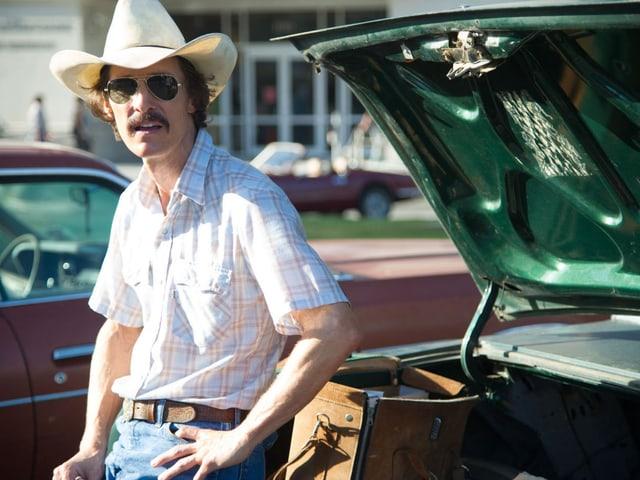 Ein Cowboy mit Hut lehnt ans Auto, der geöffnete Kofferraum hinter ihm.