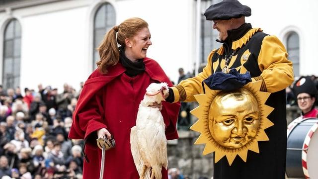 Eine Frau im roten Mantel hält eine tote Gans, daneben ein kostümierter Mann mit Sonnenmaske.