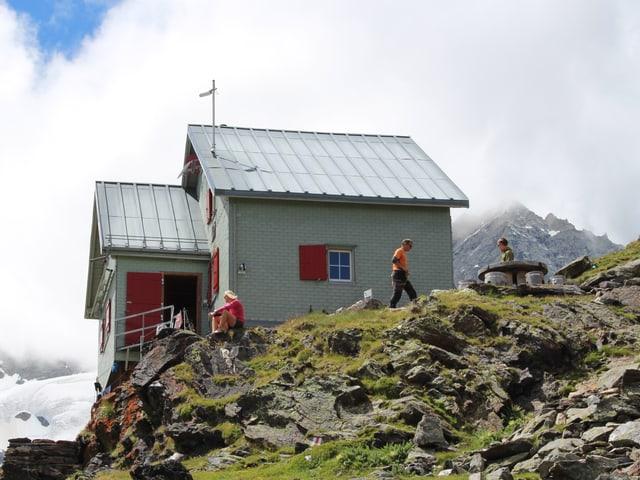Die Hütte steht auf einer felsdurchsetzten Wiese.