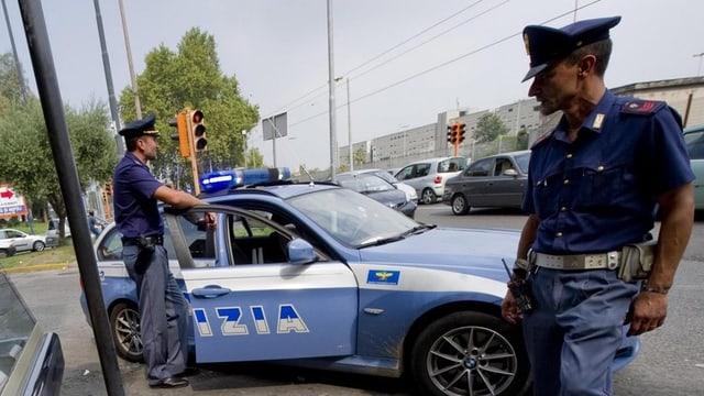 Zwei italienische Polizeibeamte vor einem Polizeiauto.