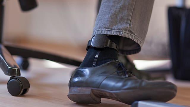 Eine elektronische Fussfessel am Bein eines Mannes