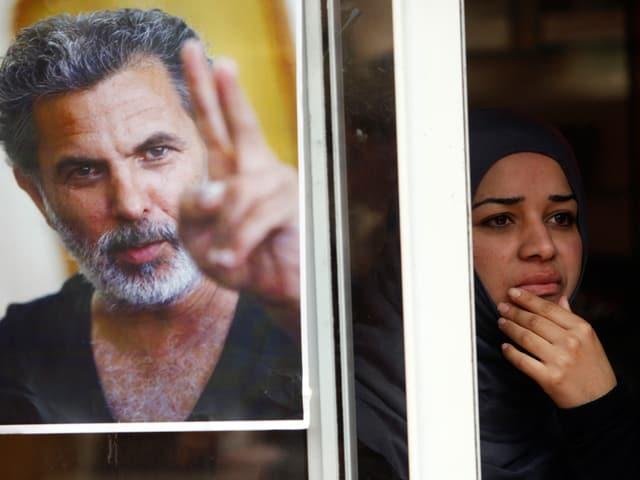 Auf dem Poster ist Mer Khamis zu sehen, wie er das Victory-Zeichen macht. Die Frau neben dem Poster ist schwarz gekleidet und blickt traurig.