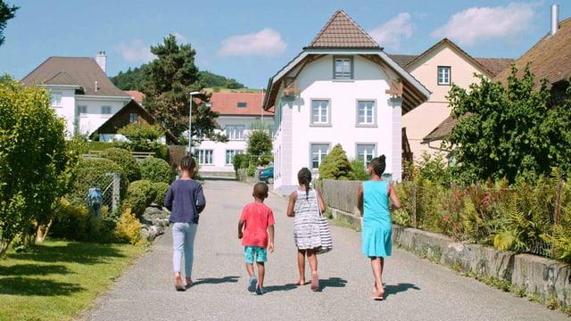 Vier Kinder mit dunkler Hautfarbe gehen im Sommer auf einer Dorfstrasse in der Schweiz