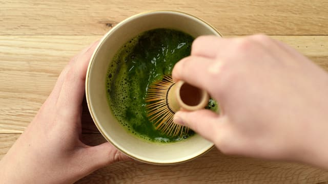 Eine Hand hält eine Teeschale, die andere schlägt den Tee mit einem Bambusbesen schaumig.