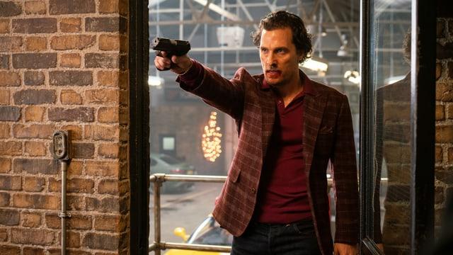 Mickey Pearson richtet seine Waffe auf jemanden ausserhalb des Bildausschnitts.