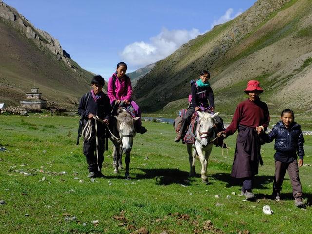 Pemain mit seiner Familie in einem grünen Tal in Nepal. Pemain und sein Vater führen je ein Pferd, auf dem jeweils eine seiner Schwestern sitzt. Die dritte, kleinste Schwester geht an der Hand ihres Vaters.