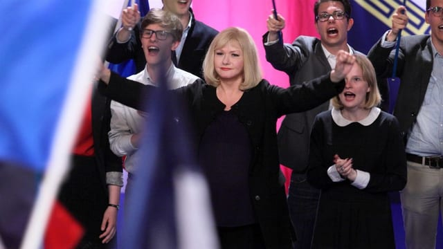Eine Frau in einer applaudierenden Menschenmenge, im Bildvordergrund eine Trikolore