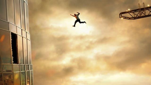 Ein Mann springt von einem Kran in ein Hochhaus