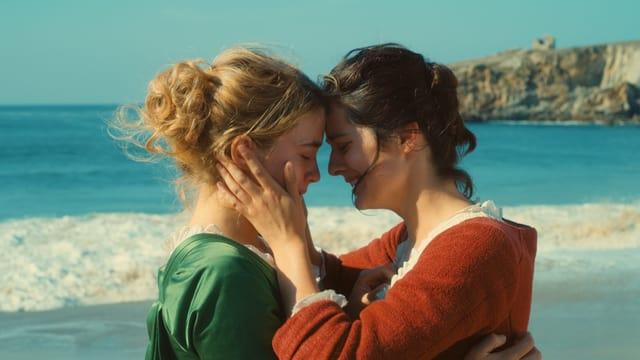 Zwei Frauen stehen nahe beieiander umarmen sich und halten ihre Köpfe nahe beieinander. Im Hintergrund sieht man das Meer.