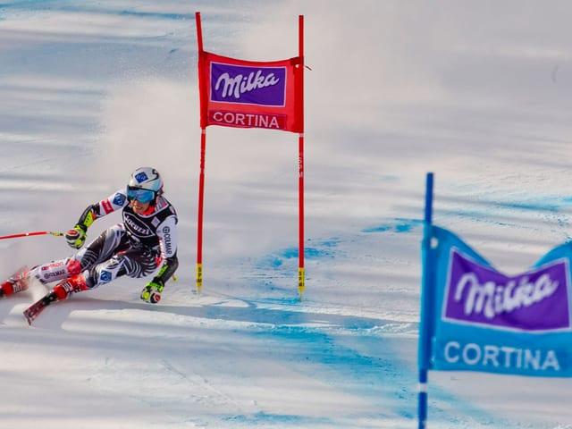 Eine Skifahrerin umkurvt zwei Tore