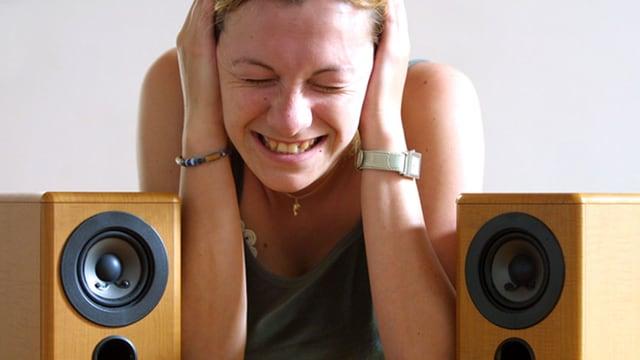 Frau sitzt zwischen Lautsprechern und hält sich die Ohren zu.