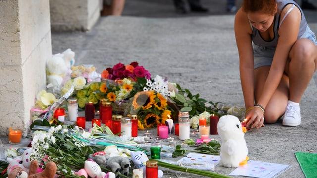 Eine Frau zündet eine Kerze an, um an die Opfer von Nizza zu gedenken.
