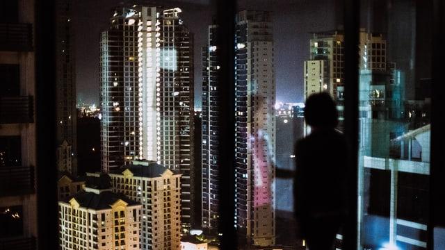 Eine Frau steht vor einen Fenster, vor ihr ist die nächtliche Skyline einer Grossstadt zu sehen.