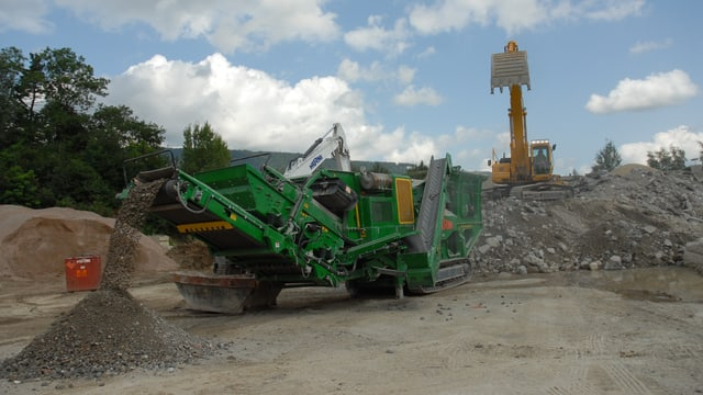 Vordergrund: Maschine mahlt Bauschutt zu Granulat, Hintergrund: Bagger schaufelt Schutt auf Maschine.