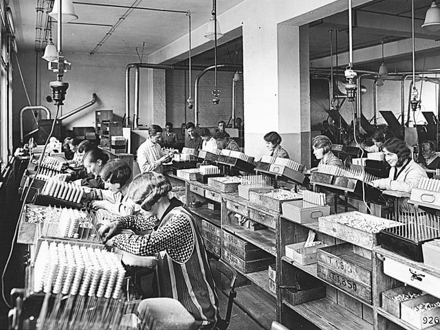 Frauen arbeiten nebeneinander in der Produktion.