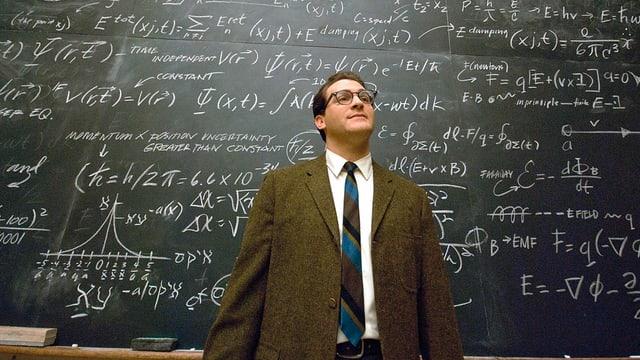 Ein Mann steht vor einer Wandtafel, die mit komplexen mathematischen Gleichungen vollgeschrieben ist.