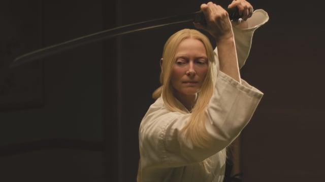 Eine Frau mit blonden, langen Haaren, weissem Kleid und einem Samurai-Schwert.