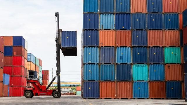Ein Gabelstapler hebt einen Schiffscontainer auf einen Containerstapel.