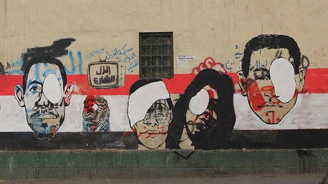 Abbildung eines Graffitos: Mehrere Köpfe tragen eine weisse Augenbinde, zwischen diesen hat einer einen Verband um den Kopf.