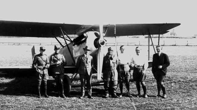 Militärs und Zivilisten vor altem Flugzeug.