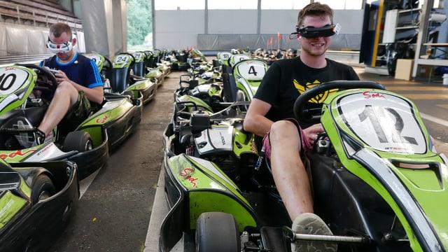 Zwei FPV-Racer sitzen in Go-Karts, mit Display-Brillen, und steuern ihre Quadrokopter.
