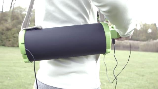 Ein Zylinderförmiger Akku hängt wie eine Handtasche am Arm des Piloten.