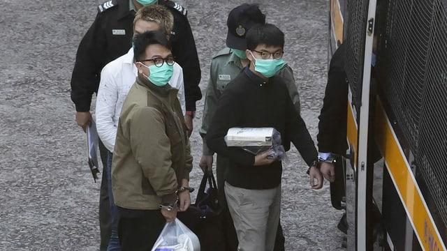 Zwei junge Männer werden in Handschellen in einen Transporter gebracht.