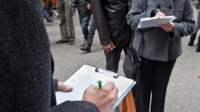 Unterschriftensammlung: Passanten füllen ein Initiativbegehren aus.