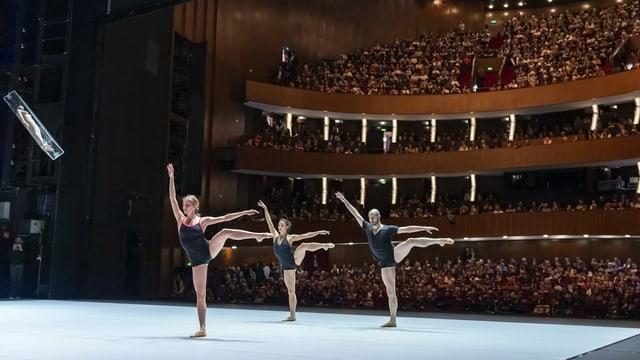 Drei Ballettänzer auf der Bühne und ein grosses Publikum im Hintergrund