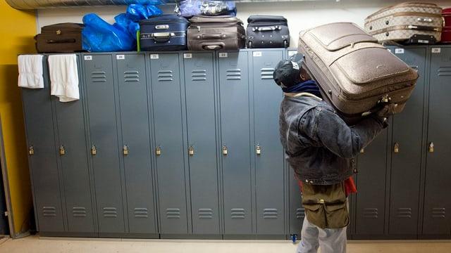 Ein Asylsuchender versorgt sein Gepäck auf einem Schrank.