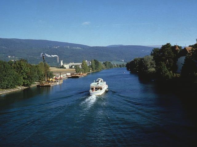 Ein Kursschiff fährt durch den mit Bäumen gesäumten Kanal. Im Hintergrund die Jurahöhen und blauer Himmel.