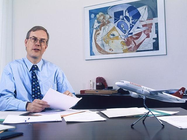 Philippe Bruggisser in seinem Büro mit Modellflugzeug auf dem Tisch.
