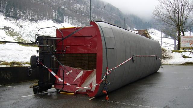 Seitwärts auf einem asphaltierten Parkplatz liegt ein Bahnwagen. Vom Wagen ist ein Wagenübergang und das Dach zu sehen. Links im Bild ist etwas erhöht das Gleis zu erkennen.