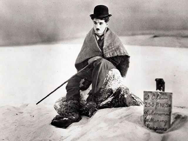 Charlie Chaplin im Schnee sitzend
